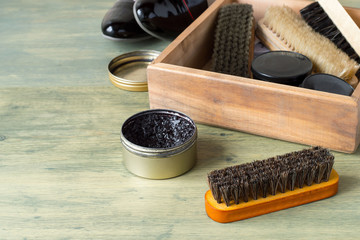 Care products for footwear. Wooden box with shoes brushes and round jars with cream on an old floor.