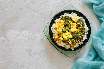 Pan Fried Sesame Tofu with Broccoli and broccolliniin, rice on black plate, tofu salad on white concrete background, light blue napkin, top view, copy space, Vegan, diet and vegetarian food concept