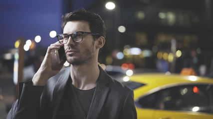 A closeup of man in a jacket is having a night call on the street, holding his cellphone. Blurred lights on the background