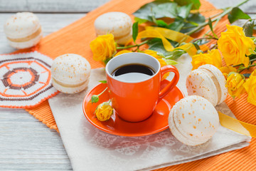 Orange cup of black coffee, yellow roses flowers and sweet pastel french macaroons