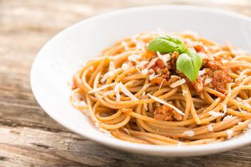 Piatto di spaghetti condito con carne, pomodoro e parmigiano