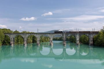 Old Steam Train crossing Soca River over Gorizia Stone Bridge, Italy