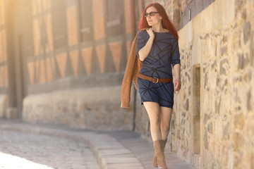 Beautiful red haired woman in short blue dress wearing sunglasses walking along a pavement of an old town in bright sunny light – beauty/fashion concept – blurred background with copy space for text