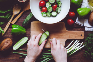 hands cutting vegetables on wooden board