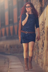 Beautiful red haired woman in short blue dress wearing sunglasses walking along a pavement of an old town in bright sunny light – beauty/fashion concept – portrait orientation, blurred background