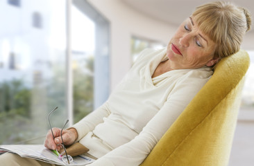 Cute senior woman falling asleep with her book and glasses in her hands lying down on the couch of the living room