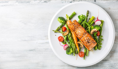 Roasted salmon steak with asparagos broccoli carrot tomatoes radish green beans and peas. Fish meal...