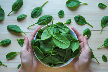 Fresh spinach leaves on a wooden table.