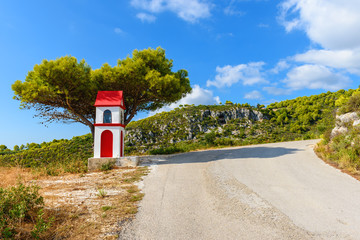 Little chapel and pine tree near the sphalt road of Zakynthos island in sunny summer day. Greece