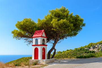 Little chapel and pine tree on coast of Zakynthos island in sunny summer day Greece