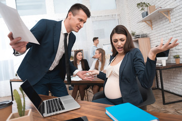 Angry young man in suit screams at pregnant girl in office. Pregnancy at work.
