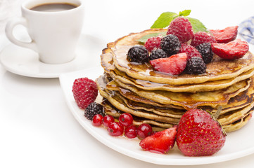 Delicious pancakes with berries and maple syrup on a white background