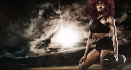 Sporty beautiful woman with dumbbells makes fitness exercising at to stay fit