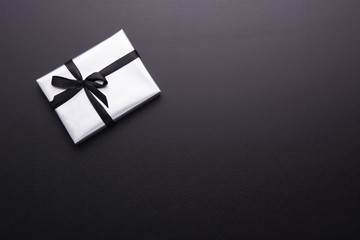 Wrapped gift box with colored ribbon as a present for Christmas, new year, mother's day, anniversary, birthday, party, on black background, top view. Present for a colleague at work.