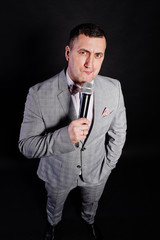 Handsome man in gray suit with microphone against black background on studio. Funny face of toastmaster and showman.