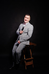 Handsome man in gray suit with microphone against black background on studio sitting on chair. Toastmaster and showman.