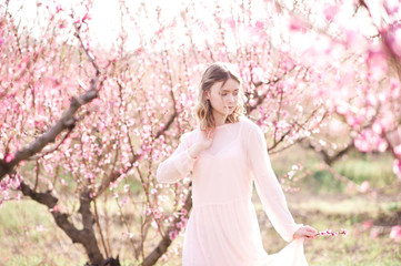 Spring portrait og blonde girl in blooming peach orchard. Spring season. 20s.