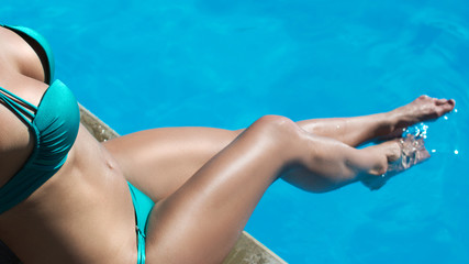 Sexy tanned woman relaxes by the pool dangling her legs in the water. Copy-space