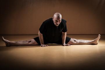 A kickboxer practicing a high kick in a indoor dojo.