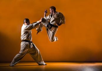 Two karate men fighting in a indoor dojo. Wall mural