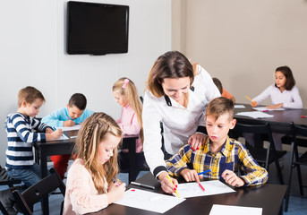 Little children with smiling teacher drawing in classroom