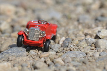 Red model oldtimer toy car driving off road