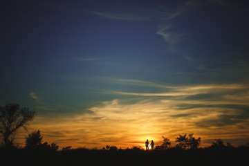 Silhouette couple in love enjoy good time together during sunset.