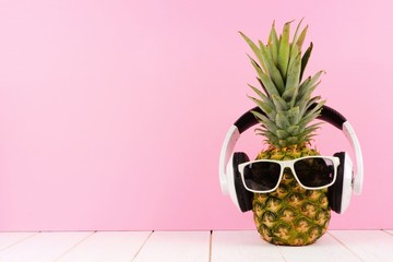 Hipster pineapple with sunglasses and headphones against a pink background. Minimal summer concept.