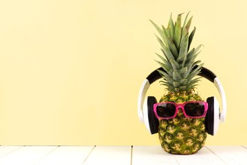 Hipster pineapple with sunglasses and headphones against a yellow background. Minimal summer concept.