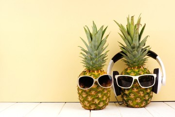 Hipster pineapples with sunglasses and headphones against a yellow background. Minimal summer concept.