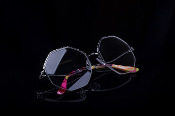 Elegant glasses on a black background with a mirror image