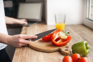 The woman cut the peppers. She watches how to prepare a dish. View the recipe on the Internet