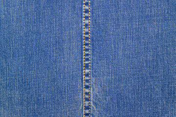 Blue denim with a vertical seam in the middle. Fabric blue background