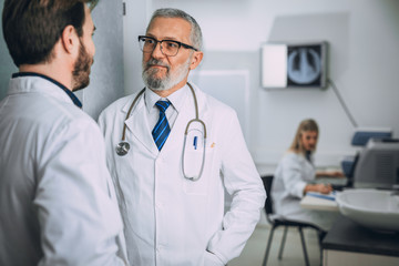 Mature doctor discussing with his colleague about the diagnosis at the hospital's office.