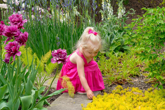 Little girl exploring a sensory garden in Spring