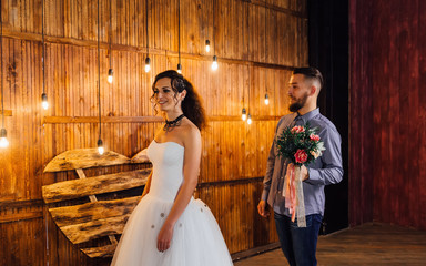 Wedding in the style of rock. Rocker or Biker wedding. Guys with stylish leather jackets. It's a rock'n'roll baby. Sweet couple in a photo studio. Steep shooting in a wooden location. Around the bulb