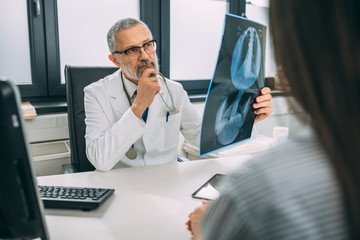 Mature doctor examining the medical x-rays image in hospital office.