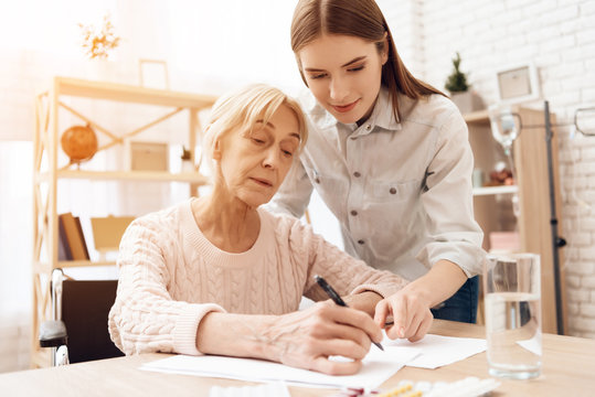 Girl is nursing elderly woman at home. Girl is helping woman write.