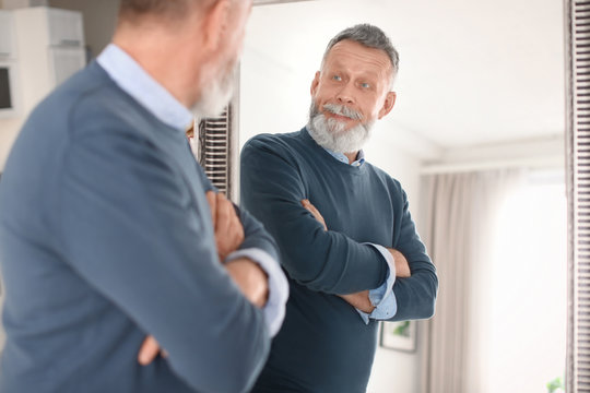 Mature man looking in mirror at home