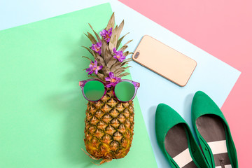 Flat lay composition with ripe pineapple, sunglasses, shoes and mobile phone on color background
