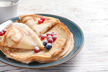 Thin pancakes served with sugar powder and berries on plate, closeup