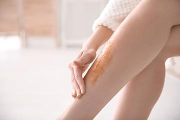 Woman applying body scrub on legs, closeup