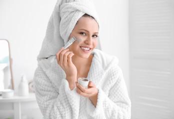 Woman applying scrub onto face in bathroom