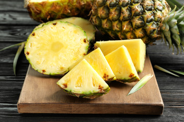 Fresh sliced pineapple on wooden board, closeup