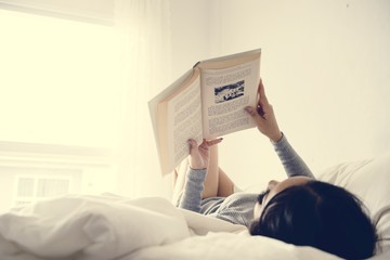 An Asian Woman Reading on a Bed in a Bright Minimal Room