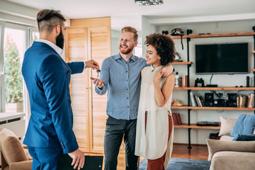 Real-estate agent giving house keys to couple in their new home.