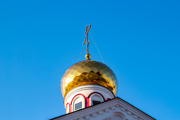Gold-plated dome of the Russian Orthodox Church against the blue sky