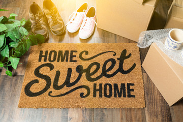 Home Sweet Home Welcome Mat, Moving Boxes, Women and Male Shoes and Plant on Hard Wood Floors Wall mural