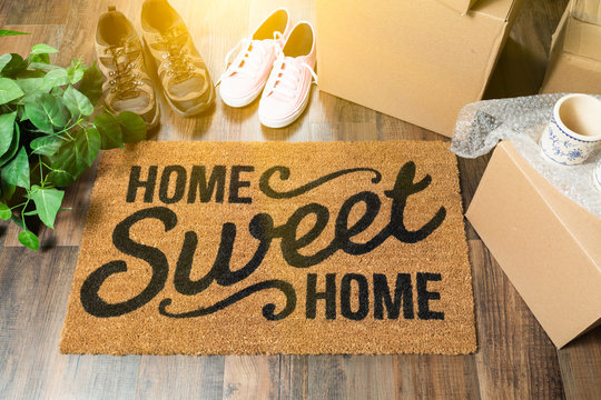 Home Sweet Home Welcome Mat, Moving Boxes, Women and Male Shoes and Plant on Hard Wood Floors