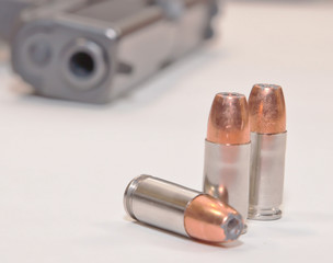 Three 9mm hollow point bullets on a white table in front of a black pistol
